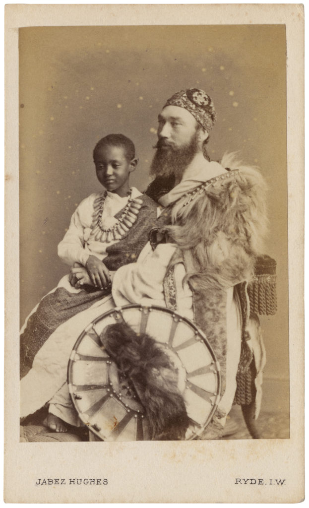 <strong> Prince (Dejatch) Alamayou and Tristram Speedy. Ryde, Isles of Wight. 1868. Photograph by Jabez Hughes. </strong><br></br>Courtesy of Autograph ABP. Supported by the National Lottery through the Heritage Lottery Fund.<br></br>PRINCE (DEJATCH) ALAMAYOU (1861–79) was the son of Emperor Tewodros II of modern-day Ethiopia (then Abysinia), who committed suicide following his capture by the British during the Battle of Magdala in 1868. The young Prince Alamayou was brought to Britain in the care of Tristram Charles Sawyer Speedy (1836–1910), an army officer and explorer. Alamayou lived with Speedy on the Isle of Wight and was presented to Queen Victoria, who is said to have been very fond of him and wrote about their encounters in her diary journals. He was educated at Cheltenham College, Rugby School, and at the Royal Military College, Sandhurst but died of pleurisy aged just eighteen. At the queen's request, he was buried in St George's Chapel, Windsor.  Jabez Hughes was photographer to the Queen and H.R.H. the Prince of Wales; his Royal Photographic Studio was locted in Ryde, Isle of Wight.<br></br>Albumen carte-de-visite,  64x100mm.