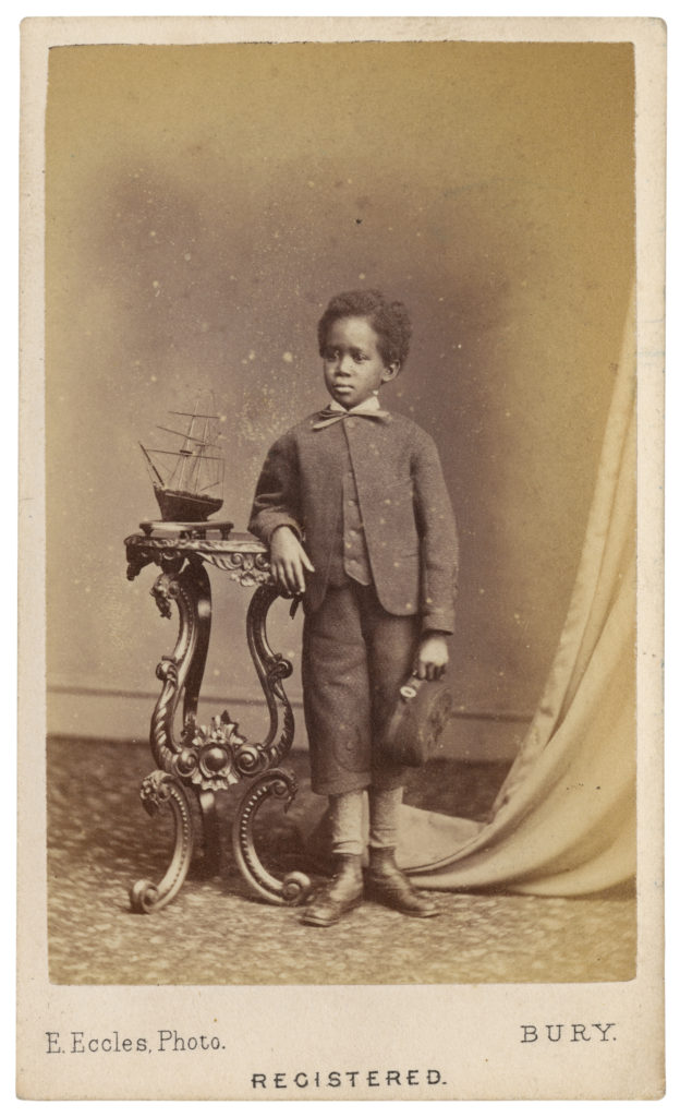 <strong> Dado. Bury, Manchester, ? 1874. Photograph by Edmund Eccles. </strong><br></br>Courtesy of Autograph ABP. Supported by the National Lottery through the Heritage Lottery Fund.<br></br>Born in East Africa, Dado was a member of the Galla people, a historic name for the Oromo, the single largest ethnic group in the Horn of Africa. He was captured by Arab slavers but later rescued when he was about seven years old by a Methodist missionary, Thomas Wakefield whom he accompanied to England in 1868. He returned to the East Africa with Wakefield and his wife Rebecca Brewin, their ship leaving Gravesend on 24 February 1870. <br></br>Albumen carte-de-visite,  64x100mm.