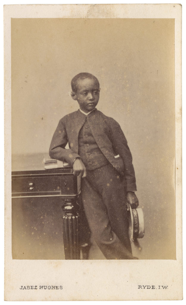 <strong> Prince Alamayou. Ryde, Isles of Wight. 1868. Photograph by Jabez Hughes.</strong><br></br>Courtesy of Autograph ABP. Supported by the National Lottery through the Heritage Lottery Fund.<br></br>PRINCE ALAMAYOU (1861–79) was the son of Emperor Tewodros II of modern-day Ethiopia (then Abysinia), who committed suicide following his capture by the British during the Battle of Magdala in 1868. The young Prince Alamayou was brought to Britain in the care of Tristram Charles Sawyer Speedy (1836–1910), an army officer and explorer. Alamayou lived with Speedy on the Isle of Wight and was presented to Queen Victoria, who is said to have been very fond of him and wrote about their encounters in her diary journals. He was educated at Cheltenham College, Rugby School, and at the Royal Military College, Sandhurst but died of pleurisy aged just eighteen. At the queen's request, he was buried in St George's Chapel, Windsor.  <br></br>Albumen carte-de-visite,  64x100mm.
