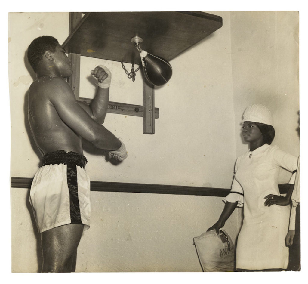 "Muhammad Ali with Drum model/reporter training for a fight at Earls' Court, London, 1967. Vintage bromide print 8 x 10 "" © James Barnor / Courtesy of Autograph ABP, London. Supported by the National Lottery through the Heritage Lottery Fund."