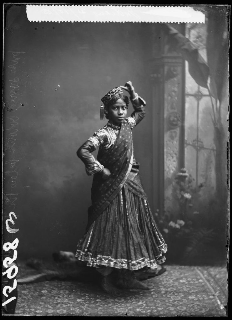 <strong>Unidentified Sitter. London, 1885. <br>By the London Stereoscopic Company.   </strong>   <br></br>  © Hulton Archive/Getty Images. Courtesy of Hulton Archive, and Autograph ABP, London. Supported by the National Lottery through the Heritage Lottery Fund. <br></br>  Portrait of a young woman performing an Indian folk 'Nautch' dance for the camera at the London Stereoscopic Company studio on 31 October 1885. In North India, Nautch is one of several styles of popular dance, performed by young women known as Nautch girls. She was part of an Indian musical troupe who performed in variety entertainment during the Victorian era. No further details about the group and its members are known at this stage.<br></br>  Fibre-based silver gelatin print, 20x24""