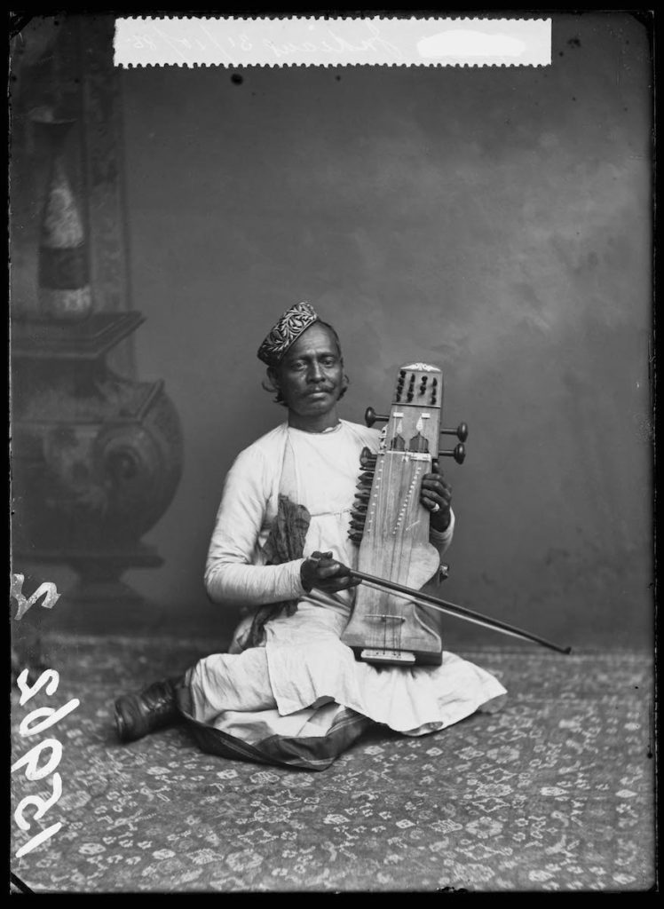 <strong>Unidentified Sitter. London, 1885. <br>By the London Stereoscopic Company.   </strong>   <br></br>  © Hulton Archive/Getty Images. Courtesy of Hulton Archive, and Autograph ABP, London. Supported by the National Lottery through the Heritage Lottery Fund. <br></br>  Portrait of a musican holding a Sarangi, a bowed string instrument photographed at the London Stereoscopic Company studio on 31 October 1885. He was part of an Indian musical troupe who performed in variety entertainment during the Victorian era. No further details about the group and its members are known at this stage. <br></br>  Fibre-based silver gelatin print, 20x24""