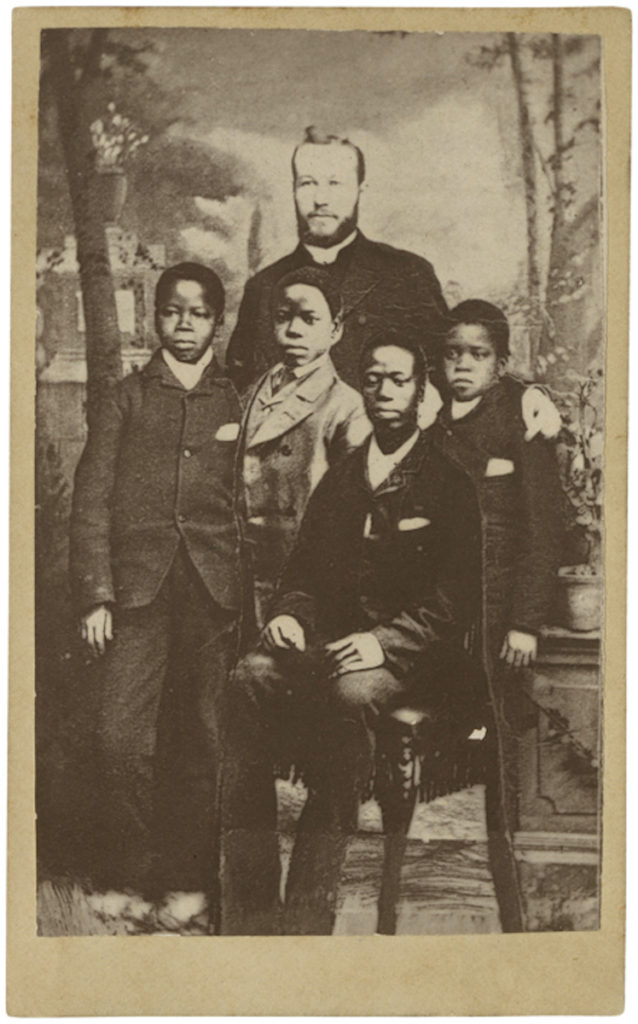 <strong> Kinkasa, Kkanza, Frank and Daniel, with Rev. William Hughes. Colwyn Bay, N. Wales, 1886. Photograph by By Lettsome & Sons.  </strong><br></br>Courtesy of Autograph ABP. Supported by the National Lottery through the Heritage Lottery Fund.<br></br>Congolese students Kinkasa (1875–88) and Nkanza Ross (1877–92) and two students named Frank and Daniel are pictured with Welsh missionary and teacher Reverend William Hughes (1856–1924) at the Congo House Training Institute for African Children in Colwyn Bay, North Wales. Hughes worked for the Baptist Missionary Society in the Congo, and in 1885 toured Britain with Congolese students, Kinkasa and Nkanza – giving fund-raising lectures and sold photographs. Kinkasa died aged just thirteen while Nkanza learnt Welsh and English, reciting any part of the New Testament from memory. He wished to return to Africa but died prematurely in 1892.<br></br>Albumen carte-de-visite,  64x100mm.