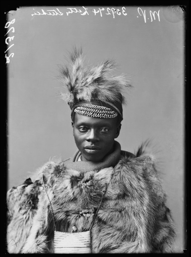 <strong>Unidentified member of The African Choir. <br>London, 1891 <br>By the London Stereoscopic Company.   </strong>   <br></br>  © Hulton Archive/Getty Images. Courtesy of Hulton Archive, and Autograph ABP, London. Supported by the National Lottery through the Heritage Lottery Fund. <br></br>  The African Choir was a group of fourteen young men and women, and two children, from South Africa, then under British rule. The choir toured Britain between 1891 and 1893 to raise funds to build a technical college on the Cape Coast, performing to great acclaim and large audiences at Crystal Palace, for members of the British aristocracy and leading political figures, and most notably for Queen Victoria at Osborne House, Isle of Wight.  Their stage repertoire was divided into two halves: one comprised Christian hymns sung in English together with popular operatic arias and choruses; the other traditional African hymns. The choir appeared in traditional African dress, and in contemporary Victorian dress in response.<br></br>  Fibre-based silver gelatin print, 20x24""