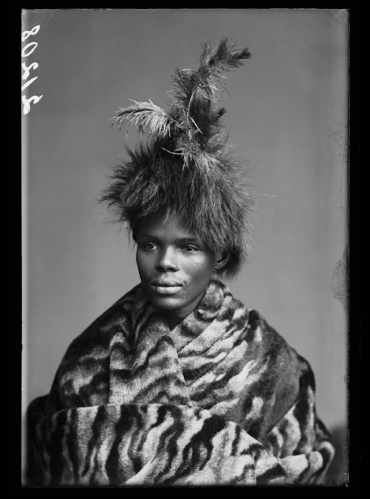 <strong>Unidentified member of The African Choir. <br> London, 1891 <br>By the London Stereoscopic Company.   </strong>   <br></br>  © Hulton Archive/Getty Images. Courtesy of Hulton Archive, and Autograph ABP, London. Supported by the National Lottery through the Heritage Lottery Fund. <br></br>  The African Choir was a group of fourteen young men and women, and two children, from South Africa, then under British rule. The choir toured Britain between 1891 and 1893 to raise funds to build a technical college on the Cape Coast, performing to great acclaim and large audiences at Crystal Palace, for members of the British aristocracy and leading political figures, and most notably for Queen Victoria at Osborne House, Isle of Wight.  Their stage repertoire was divided into two halves: one comprised Christian hymns sung in English together with popular operatic arias and choruses; the other traditional African hymns. The choir appeared in traditional African dress, and in contemporary Victorian dress in response.                                     <br></br>  Fibre-based silver gelatin print, 20x24""