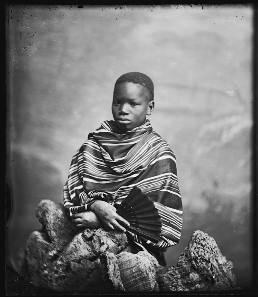 <strong>Ndugu M'Hali (Kalulu). London, 1872.  <br>By the London Stereoscopic Company.   </strong>   <br></br>  © Hulton Archive/Getty Images. Courtesy of Hulton Archive, and Autograph ABP, London. Supported by the National Lottery through the Heritage Lottery Fund. <br></br>   Ndugu M'Hali (c.1865–77), known as Kalulu, was the personal servant and companion to explorer Sir Henry Morton Stanley. He was given to Stanley as a 'slave' by an Arab merchant in present day Tanzania during the explorer's quest to find the missing Dr David Livingstone. Named Kalulu by Stanley, he was educated in London and accompanied Stanley on his travels to Europe, America and the Seychelles. He inspired Stanley's 1873 fictional novel 'My Kalulu, Prince, King and Slave: A Story of Central Africa'. He died tragically during an expedition in 1877 in the Lualaba River, the headstream of the River Congo. Stanley later renamed these rapids 'Kalulu Falls' in his memory.  <br></br>  Fibre-based silver gelatin print, 20x24""